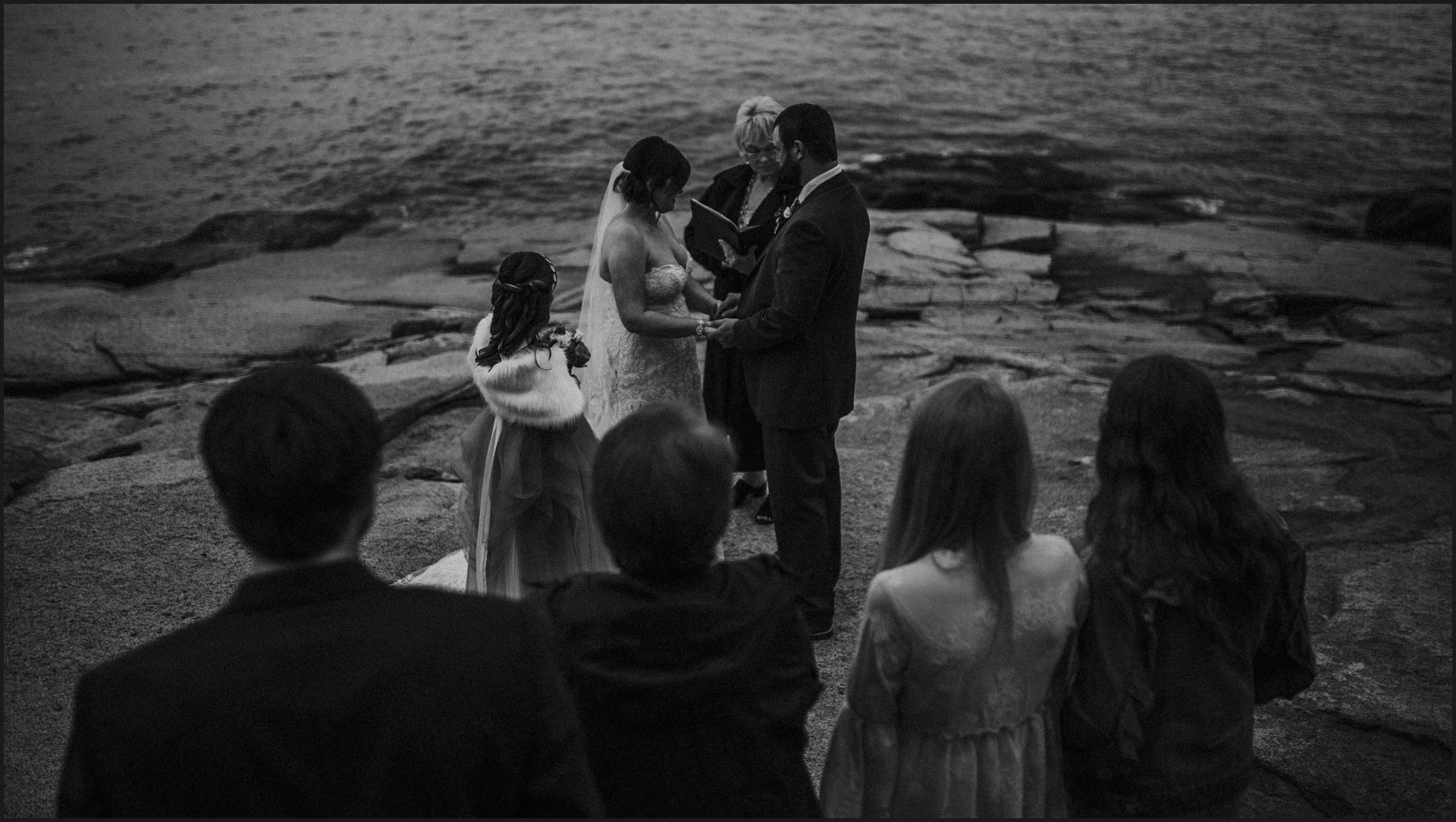 wedding, ceremony, celebrant, bride and groom, hand in hand, wedding by the sea, ocean view, wedding guests, black and white, cliff