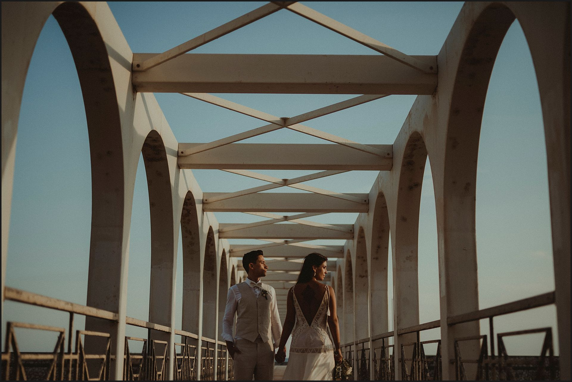 bride and groom, italy, bride, groom, hand in hand, wedding portrait, natural light, bridge, symmetry, grometries, seaside, sunset, warm light